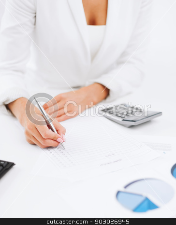 businesswoman working with calculator in office stock photo, office, business, tax, accounting concept - businesswoman working with calculator in office by Syda Productions