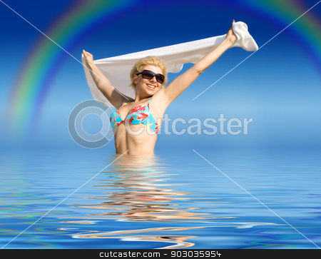 happy girl with towel standing in water stock photo, picture of happy girl with towel standing in water by Syda Productions