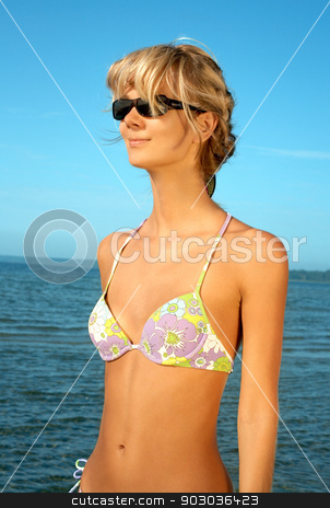 beach babe standing in water  stock photo, lovely blond in bikini standing in water  by Syda Productions