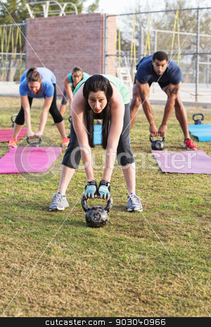 Adults Exercising Outdoors stock photo, Serious young woman and other adults working with weights by Scott Griessel
