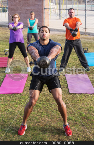 Strong Man Leading Kettle Bell Training stock photo, Strong man with tattoo leading kettle bell weight training by Scott Griessel