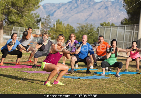 Diverse Group Adults Exercising stock photo, Serious boot camp exercise class squatting with weights by Scott Griessel
