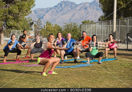 Fitness Class Squatting stock photo, Fitness group squatting with kettle bell weights by Scott Griessel