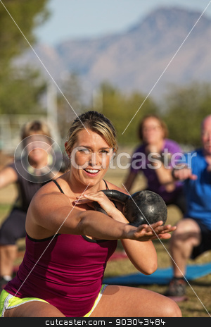 Smiling Fitness Instructor with Class stock photo, Smiling fitness instructor working out with students by Scott Griessel