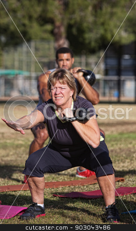 Middle Aged Woman In Workout Class stock photo, Strong middle aged woman squatting with kettle bell weights by Scott Griessel