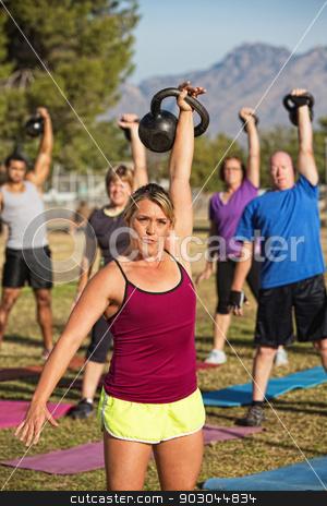 Woman Teaching Fitness Class stock photo, Athletic woman teaching boot camp fitness class outdoors by Scott Griessel
