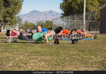 Adults Doing Push Ups stock photo, Young woman leading group in push up exercises outdoors by Scott Griessel