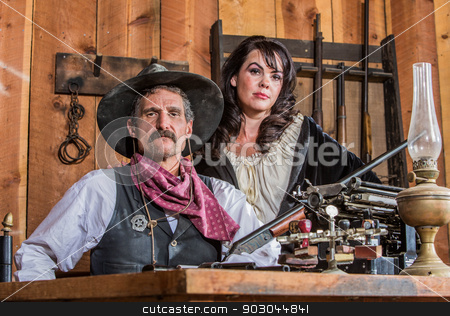 Gruff Cowboy Poses With Saloon Girl stock photo, Gruff Cowboy Poses With A Rifle And Stern Saloon Girl by Scott Griessel