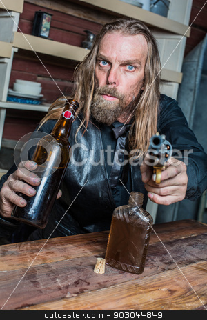 Drunk Western Man at Table stock photo, Drunk Western Man Aims Gun Towards You as he Sits at Table by Scott Griessel