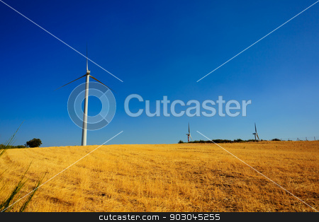 Aeolian energy in Calabria stock photo, Wind turbins producing aeolian energy under blue sky on a green field of Calabria. The sky is enhanced with a polarizer filter by Natalia Macheda