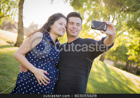 Pregnant Wife and Husband Taking Cell Phone Picture of Themselve stock photo, Pregnant Wife and Husband Taking Cell Phone Picture of Themselves Outdoors At The Park. by Andy Dean