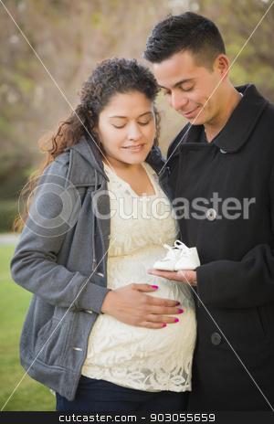 Hispanic Pregnant Couple Holding Baby Shoes Outside stock photo, Happy Hispanic Pregnant Couple Holding Baby Shoes Outside in the Park. by Andy Dean