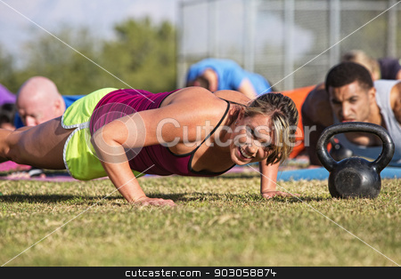 Embarrassed Woman Doing Push-Ups stock photo, Embarrassed woman doing push-ups with group outdoors by Scott Griessel