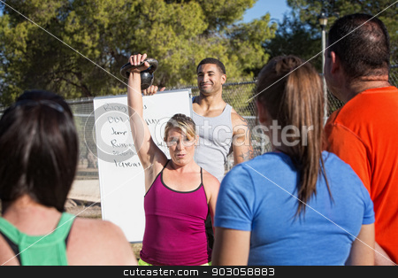 Insructor Demonstrating Kettle Bell Lifting stock photo, Fitness instructors demonstrating how to lift kettle bell weights by Scott Griessel