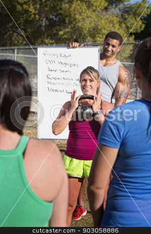 Kettle Bell Weight Explanation stock photo, Smiling fitness instructors demonstrating weight lifting to a class by Scott Griessel