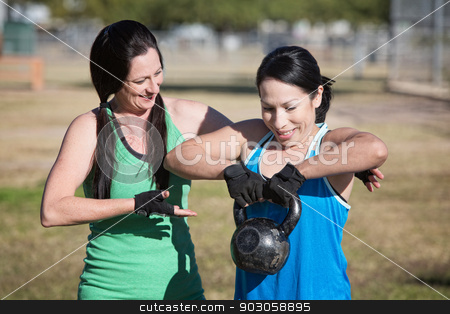 Woman Assisting Student with Weights stock photo, Friendly fitness instructor helping student use kettle bell weight by Scott Griessel