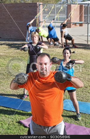 Confident Man and Group Exercising stock photo, Confident man and group lifting weights in boot camp fitness class by Scott Griessel