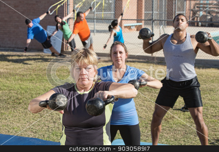 Mature Woman and Group Exercising Outdoors stock photo, Mature woman and group exercising in outdoor boot camp fitness class by Scott Griessel
