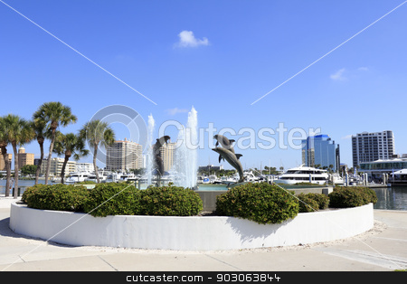 Dolphin Fountain near Downtown stock photo, SARASOTA, FLORIDA - MAY 9, 2013: Dolphin Fountain sculpted by Steven C. Dickey, donated by Marina Jacks at the end of Sarasota Island Park and Marina with downtown buildings in the background. by Lee Serenethos