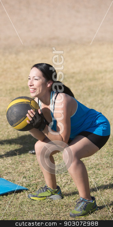 Smiling Woman Working Out stock photo, Smiling woman exercising with medicine ball outdoors by Scott Griessel