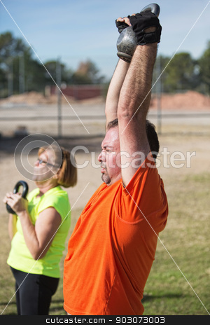 Fit Middle Aged People Exercising stock photo, Pair of fit mature adults lifting weights outdoors by Scott Griessel