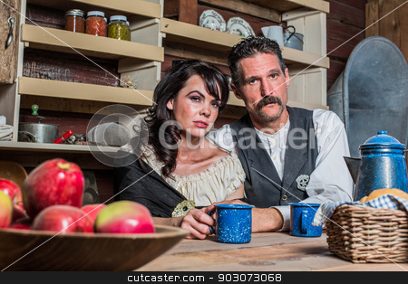 Western Sheriff and Woman Pose Inside House  stock photo, Stern looking western sheriff and woman pose inside of a house by Scott Griessel