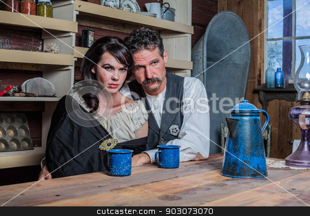 Serious Western Sheriff and Woman Pose Inside House  stock photo, Serious looking western sheriff and woman pose inside of a house by Scott Griessel