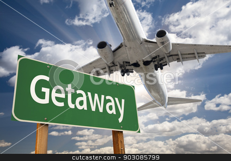 Getaway Green Road Sign and Airplane Above stock photo, Getaway Green Road Sign and Airplane Above with Dramatic Blue Sky and Clouds. by Andy Dean