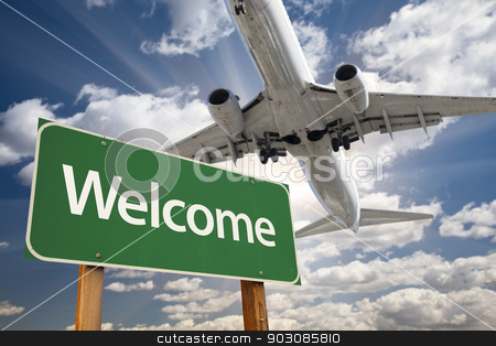 Welcome Green Road Sign and Airplane Above stock photo, Welcome Green Road Sign and Airplane Above with Dramatic Blue Sky and Clouds. by Andy Dean