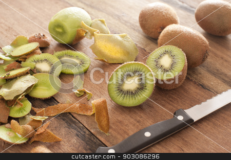 Fresh kiwi fruit being prepared for dessert stock photo, Closeup view of fresh kiwi fruit being prepared for dessert with a knife on a wooden kitchen counter by Stephen Gibson