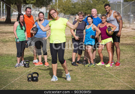 Confident Mature Woman Flexing stock photo, Confident mature woman flexing arms with fitness group standing by Scott Griessel