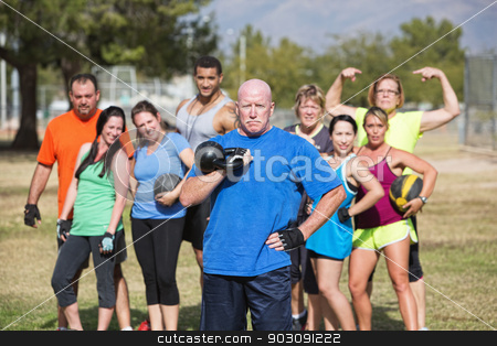 Strong Man Holding Weights stock photo, Serious middle aged man with weights and fitness group by Scott Griessel