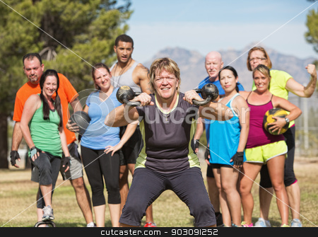Fit Mature Woman Lifting Weights stock photo, Grinning mature woman lifting kettle bell weights with group by Scott Griessel