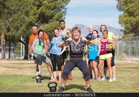 Happy Woman Lifting Weights stock photo, Smiling woman lifting kettle bell weights with group outdoors by Scott Griessel