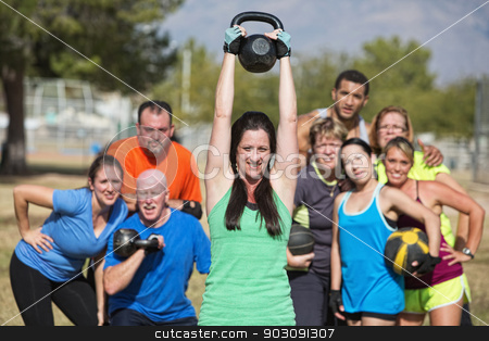 Smilng Lady Lifting Kettle Bell stock photo, Group of people watching woman lifting kettle bell weights by Scott Griessel