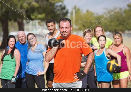 Man Holding Kettle Bell Weight stock photo, Group watching man hold kettle bell weights by Scott Griessel