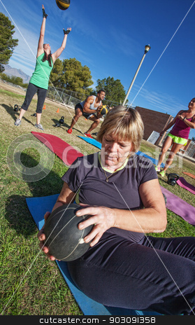 Woman Doing Sit-Ups stock photo, Mature woman doing sit-ups with medicine ball in fitness class by Scott Griessel