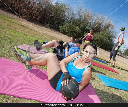 Serious Woman Doing Sit-Ups stock photo, Boot camp fitness class working out on mats outdoors by Scott Griessel