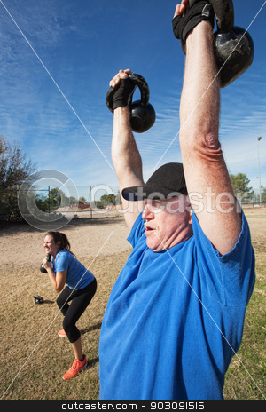 Two Adults Exercising Outdoors stock photo, Young female and mature male working with weights outdoors by Scott Griessel