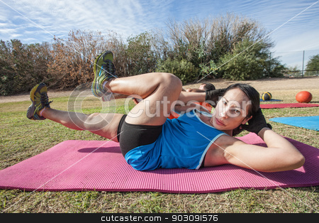 Serious Woman Doing Crunches stock photo, Hispanic female doing abdominal crunches in outdoor exercise class by Scott Griessel
