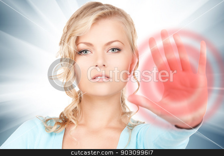 woman making stop gesture stock photo, bright picture of young woman making stop gesture by Syda Productions
