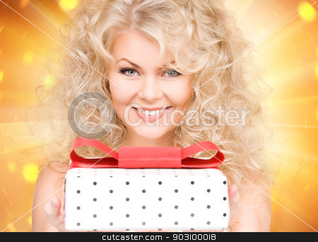 happy girl with gift box stock photo, happy girl with gift box over golden background by Syda Productions