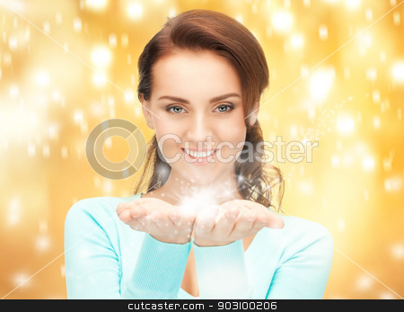 magic on the palms stock photo, beautiful woman with magic on the palms of her hands by Syda Productions