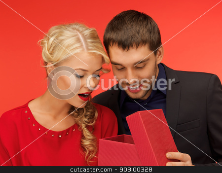 man and woman looking inside the gift box stock photo, picture of man and woman looking inside the box (focus on man) by Syda Productions