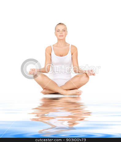 woman practicing lotus pose on white sand stock photo, woman in cotton undrewear practicing yoga lotus pose on white sand by Syda Productions