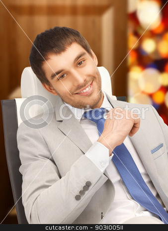 young businessman sitting in chair stock photo, picture of young businessman sitting in chair by Syda Productions