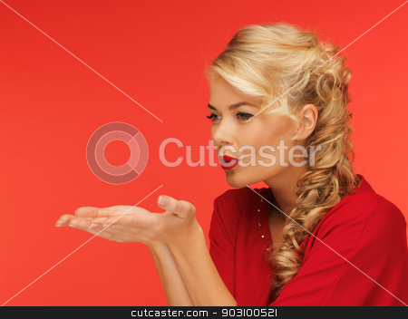 woman blowing something on the palms of her hands stock photo, lovely woman in red dress blowing something on the palms of her hands by Syda Productions