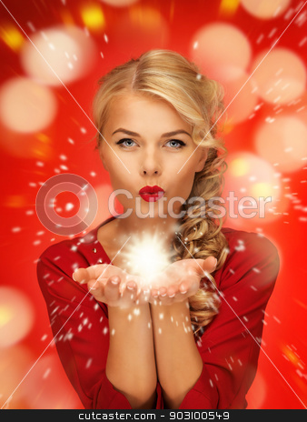 woman blowing magic on the palms of her hands stock photo, lovely woman in red dress blowing magic on the palms of her hands by Syda Productions