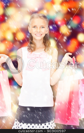 little shopper stock photo, happy girl with shopping bags over christmas lights by Syda Productions