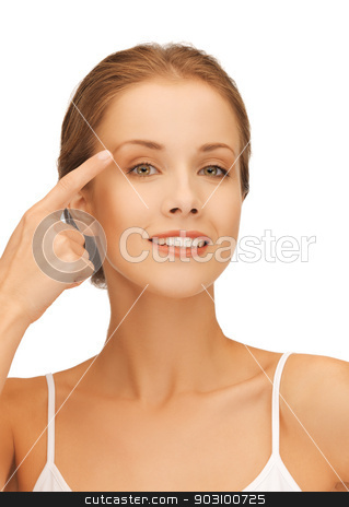 beautiful woman pointing to eyebrow stock photo, picture of beautiful woman pointing to eyebrow by Syda Productions